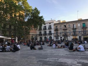 Young people lounging on the cement at Plaça del Sol