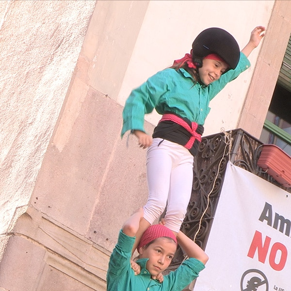 Young girl standing atop a human castle during production of Catalunya Barcelona film