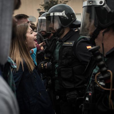 A woman faces off with police in Barcelona in 2017