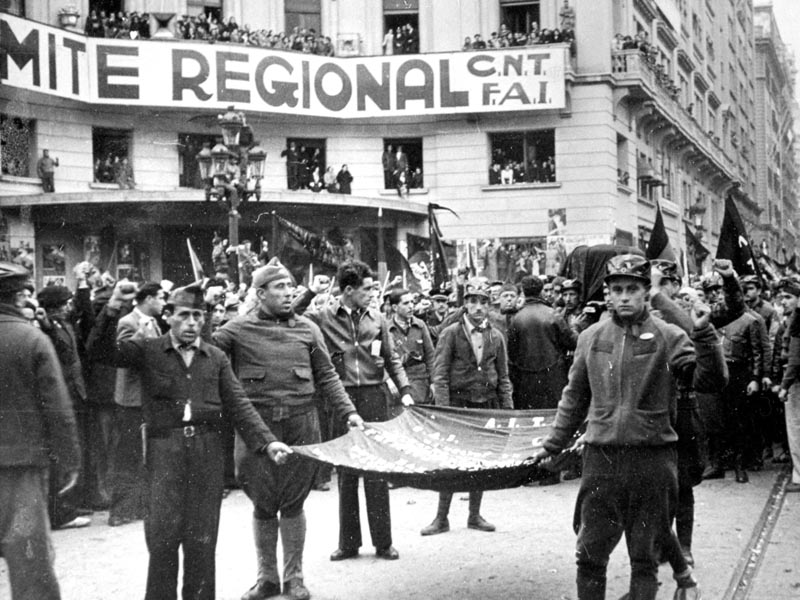 1936 - Republican miitia members, in front of CNT FAI headquarters, carry flag and coffin of Durruti.
